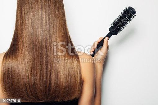 istock Woman standing with her back and demonstrates luxurious hairstyle 910797916