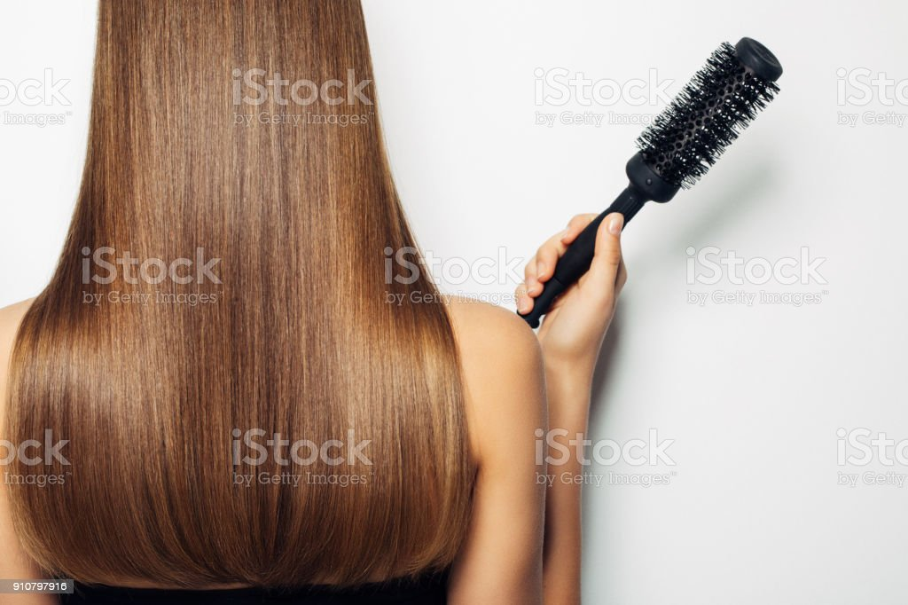 Woman standing with her back and demonstrates luxurious hairstyle stock photo