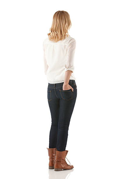 woman standing with her hands in pockets - back stock pictures, royalty-free photos & images