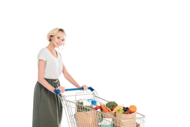 frau stehend mit einkaufswagen und lächelt in die kamera - trolley kaufen stock-fotos und bilder