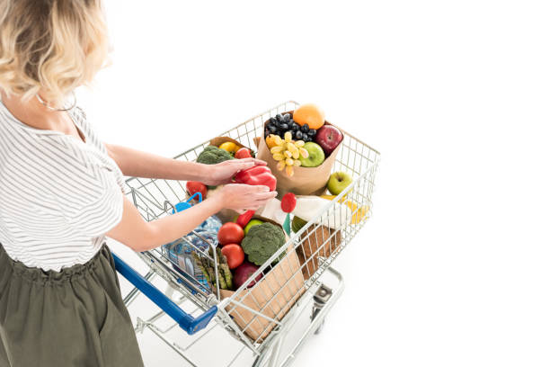 frau mit einkaufswagen voller lebensmittel - trolley kaufen stock-fotos und bilder