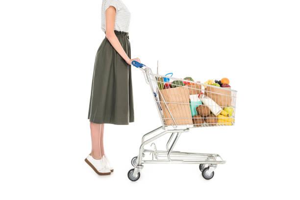 frau mit einkaufswagen mit papiertüten - trolley kaufen stock-fotos und bilder