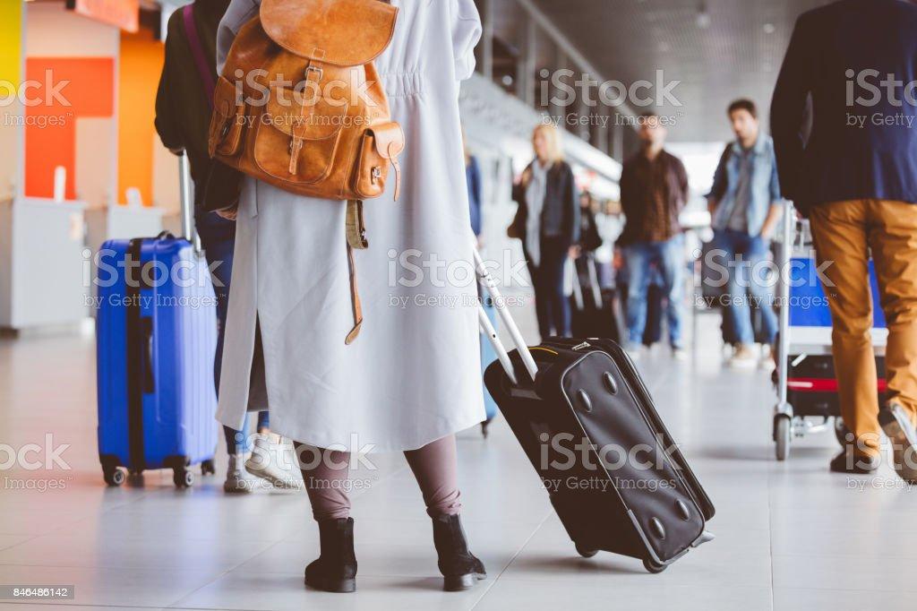 Frau mit Koffer am Flughafen-terminal Lizenzfreies stock-foto