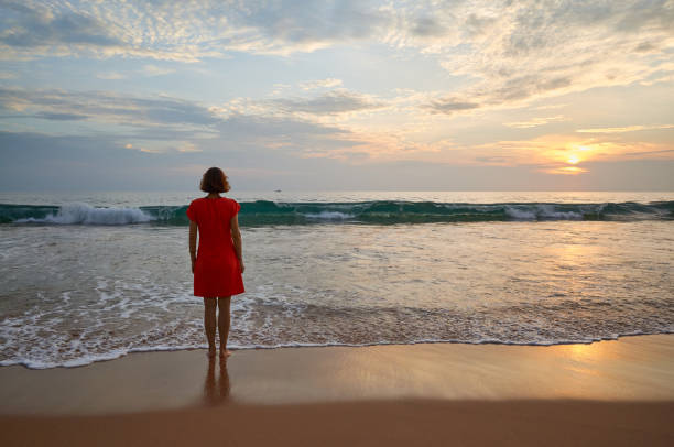 Woman stands alone on a beach looking at horizon at sunset. stock photo