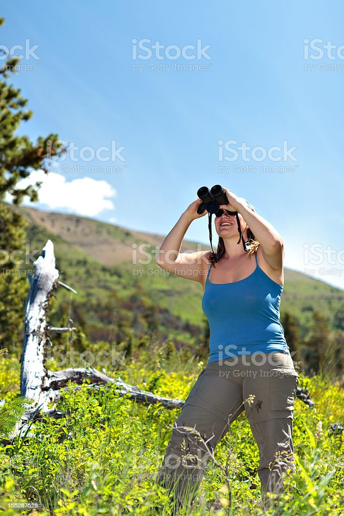 Woman Stands and Surveys with Binoculars stock photo