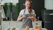 istock A woman stands in an apron in the kitchen and spreads peanut butter on toast 1306095131