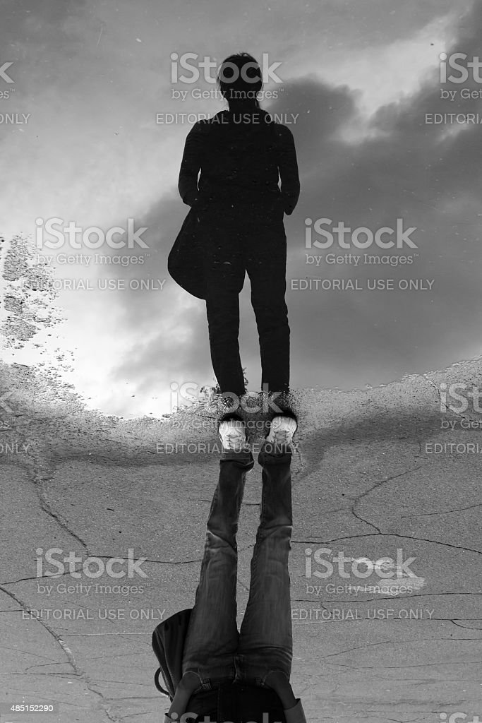 Woman Stands in Rain Water Puddle Reflection stock photo