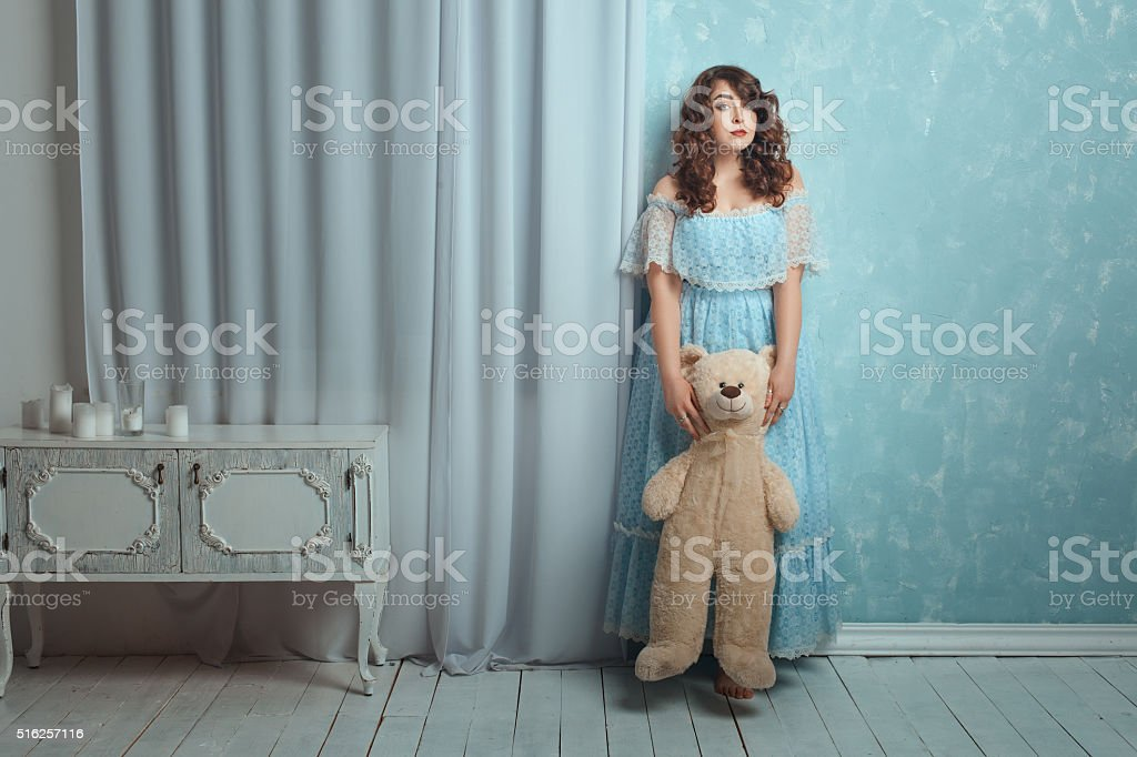 Woman stands near wall with a bear toy. stock photo