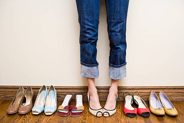 woman stands wearing heels with her collection of shoes - shoe stock photos and pictures