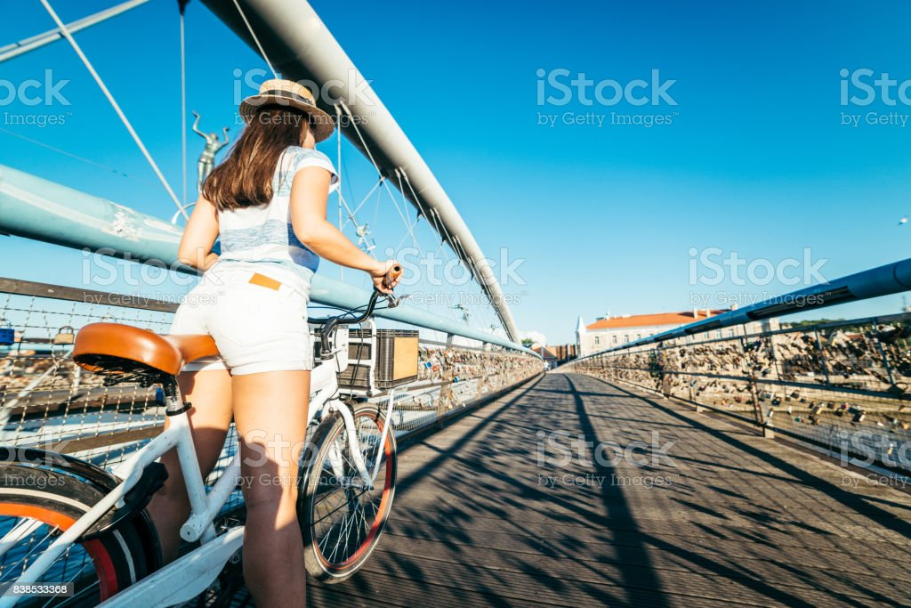 woman stands with bicycle in the middle of the bridge stock photo