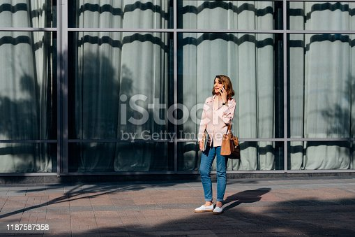 Pretty Caucasian senior woman standing outdoors at the city and talking on her cell phone.