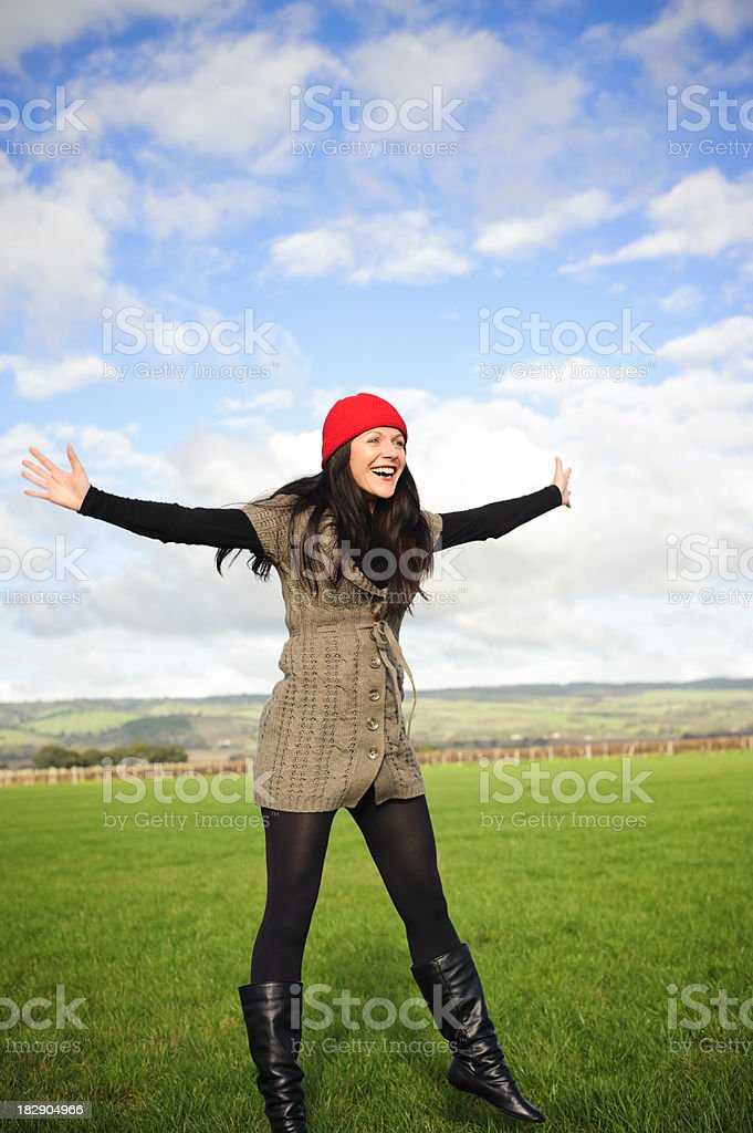 Woman star jumps smiling with red wool hat stock photo