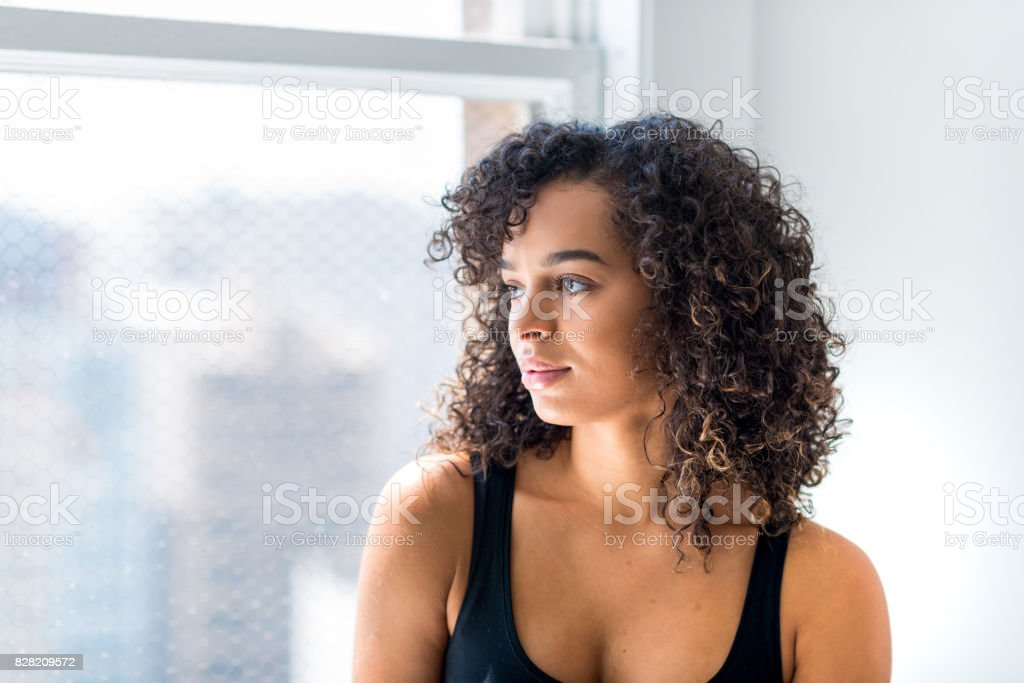 Woman Stares Out of the Window of Her Loft stock photo
