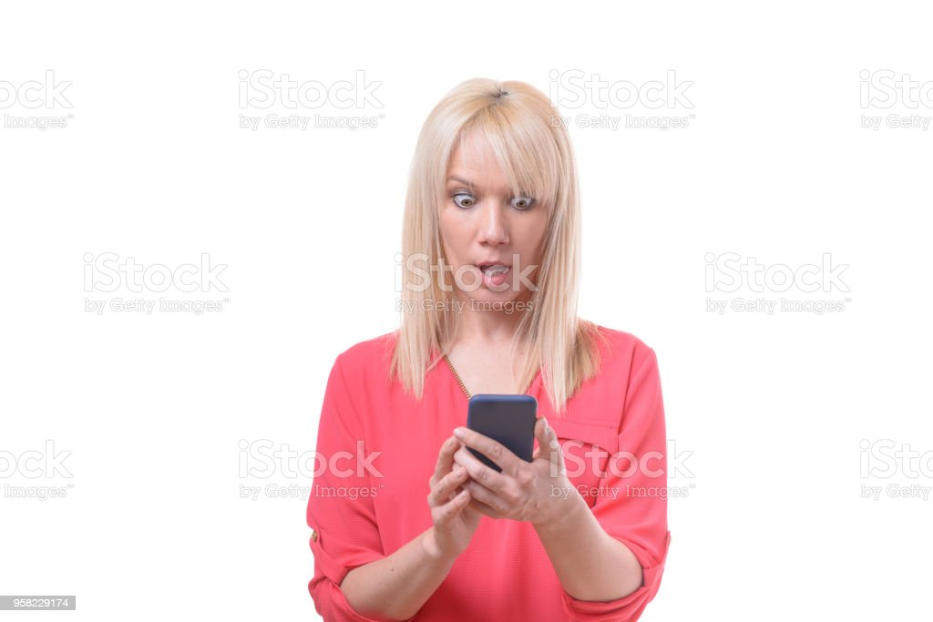 Woman staring at her mobile in astonishment stock photo