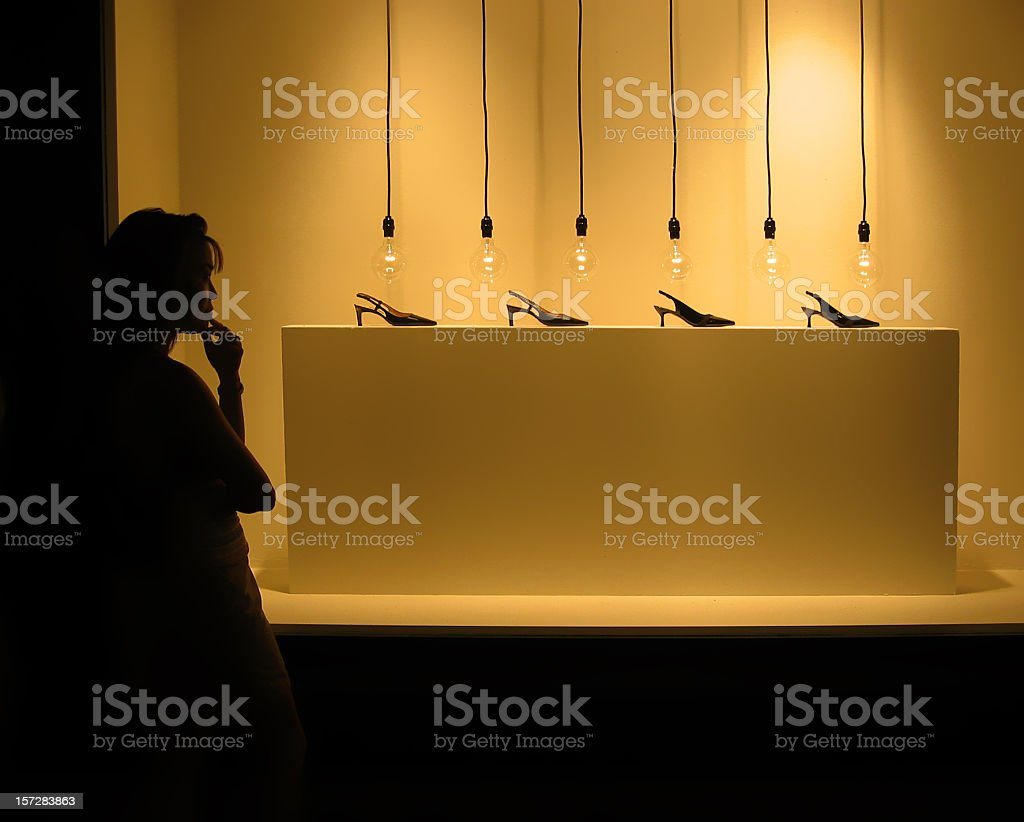 Woman staring at shoes with light bulbs stock photo