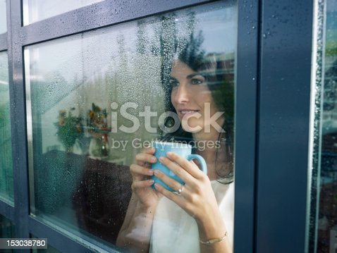 mid adult woman drinking coffee and looking out of the window on rainy day. Horizontal shape