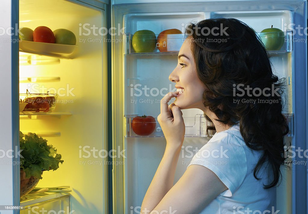 Woman staring into a fridge full of food stock photo