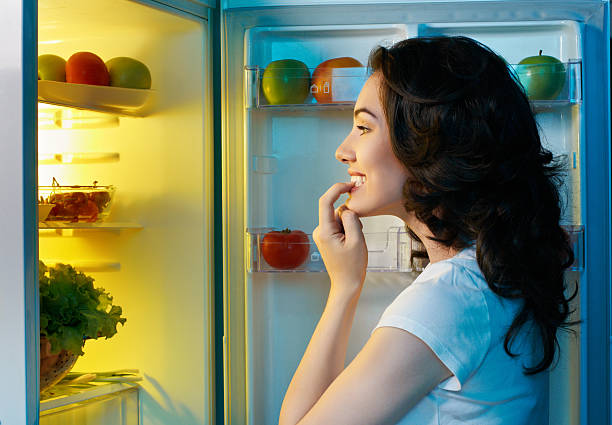 Woman staring into a fridge full of food a hungry girl opens the fridge midnight stock pictures, royalty-free photos & images
