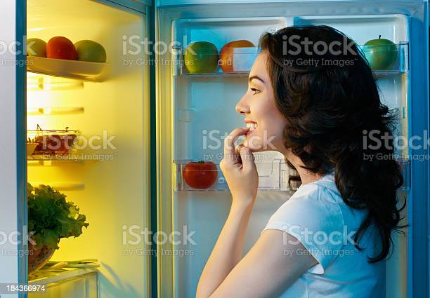 Woman Staring Into A Fridge Full Of Food Stock Photo - Download Image Now