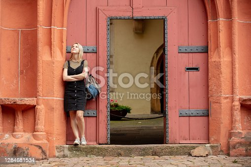 woman stay near old red doors in roman style in Europe