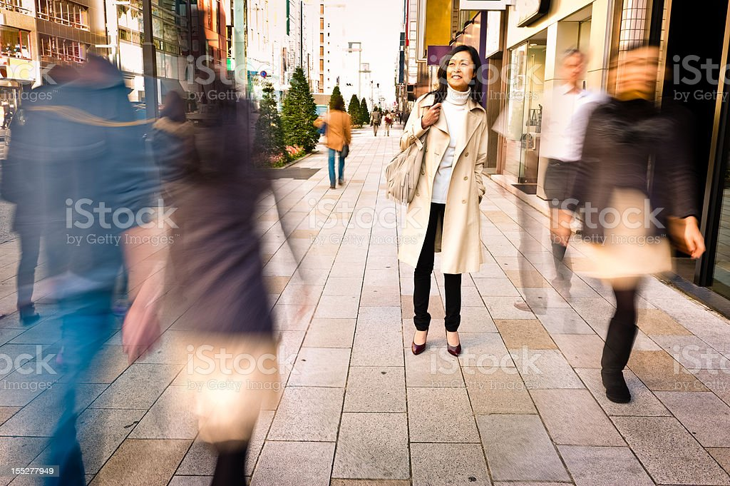 Woman Staying in a Crowded Street stock photo