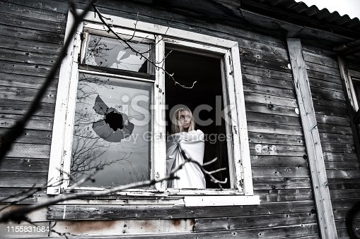 Woman in a white shirt staying near the broken window
