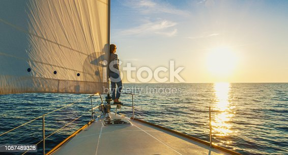 Woman staying on edge of prow and looking at sunset, Croatia