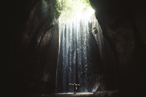 istock Woman staying under hidden waterfall in cave on Bali 1082359040