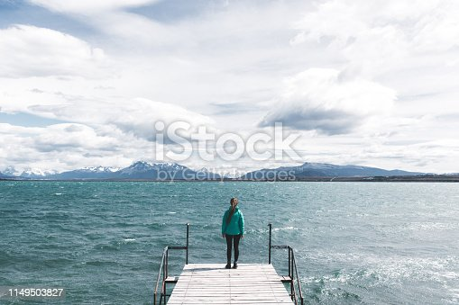 Young woman in green jacket enjoying the view of dramatic sky, Andes mountains and Pacific Ocean during the storm in Puerto Natales city, Patagonia, Chile