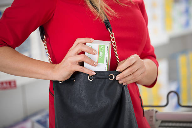 Woman Stealing Capsule Packet At Supermarket Midsection of woman stealing capsule packet at supermarket inserting stock pictures, royalty-free photos & images