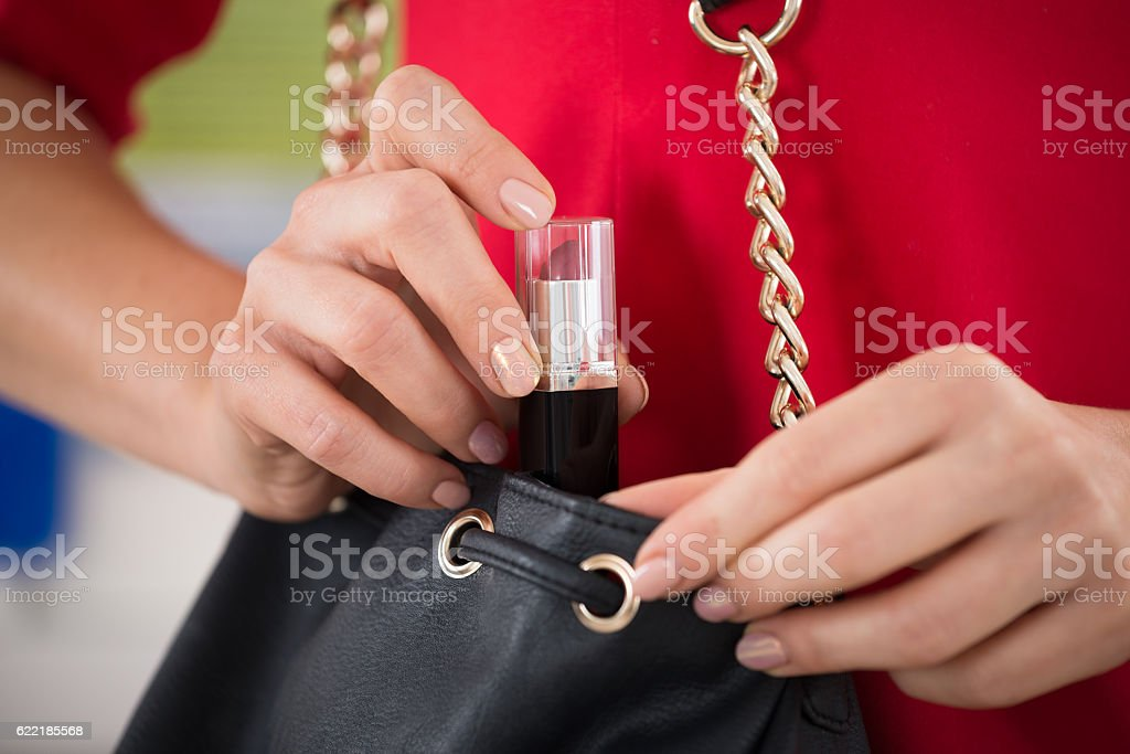 Woman Stealing Lipstick At Supermarket stock photo