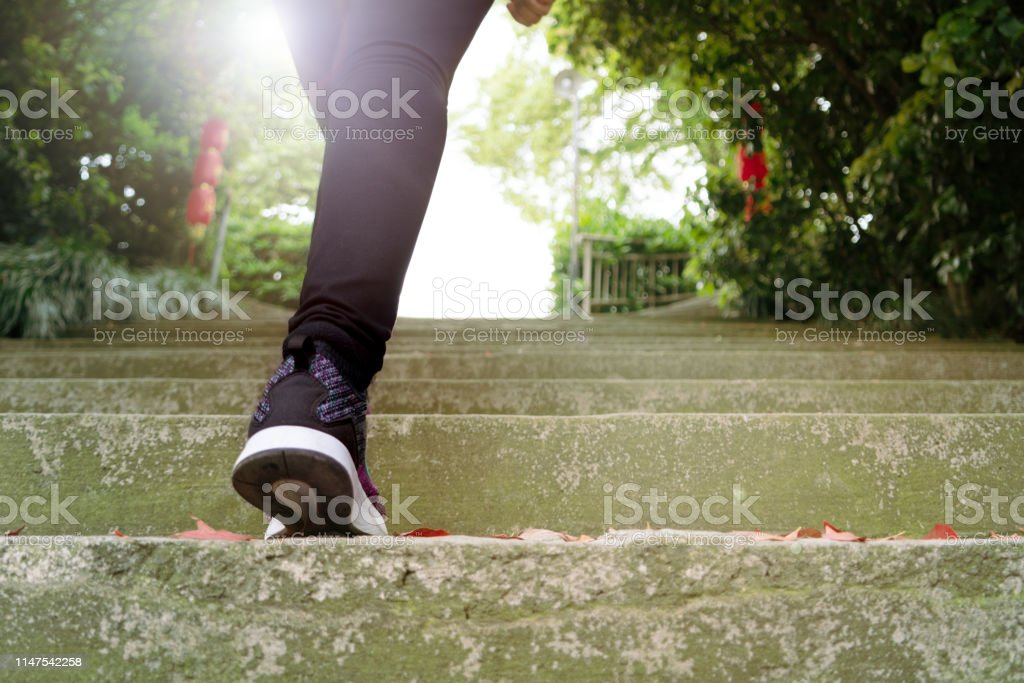 woman step up to success, traveler is climbing on stone step in China