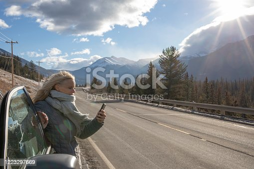 527894422 istock photo Woman steps out of her car to look for directions on cell phone 1223297669