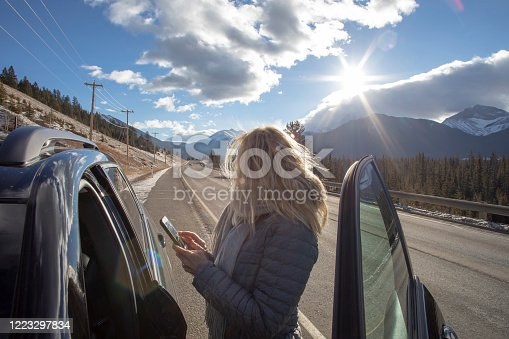 527894422 istock photo Woman steps out of her car to look for directions on cell phone 1223297834