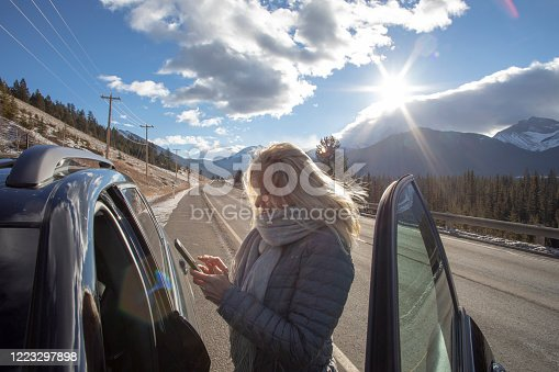 527894422 istock photo Woman steps out of her car to look for directions on cell phone 1223297898
