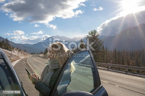 527894422 istock photo Woman steps out of her car to look for directions on cell phone 1223297899
