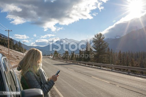 527894422 istock photo Woman steps out of her car to look for directions on cell phone 1223298599