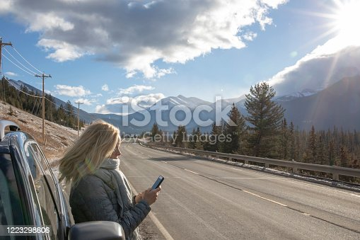 527894422 istock photo Woman steps out of her car to look for directions on cell phone 1223298606