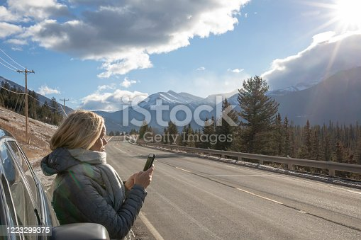 527894422 istock photo Woman steps out of her car to look for directions on cell phone 1223299375