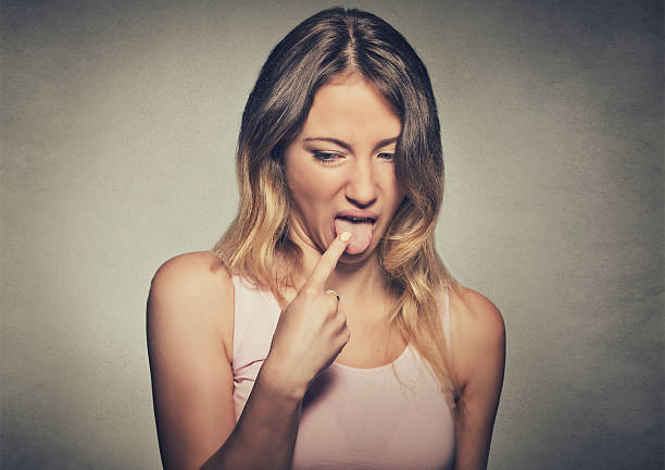 woman sticking finger in throat about to throw up Closeup portrait young woman, annoyed, frustrated fed up sticking her finger in her throat showing she is about to throw up isolated on gray wall background disgust stock pictures, royalty-free photos & images