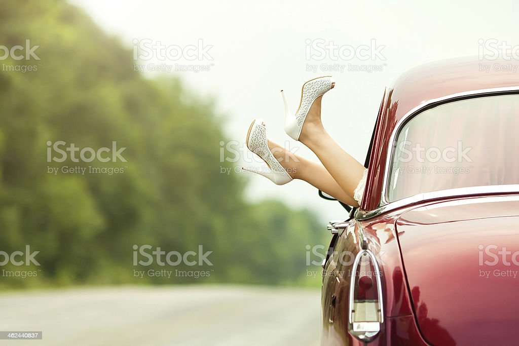 Woman sticking her feet outside of a classic car stock photo