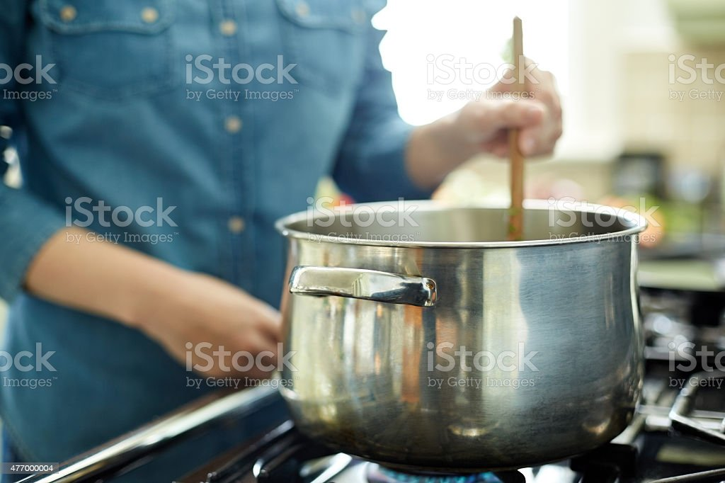 Woman stirring food in cooking pot with wooden spoon stock photo