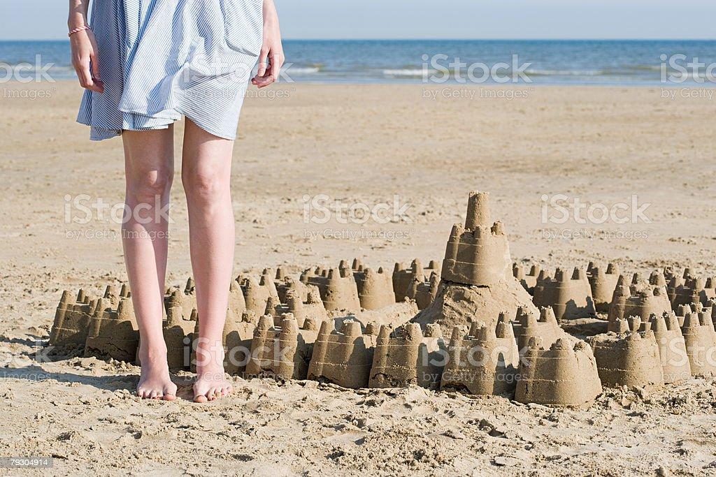 Woman stood next sandcastle 免版稅 stock photo