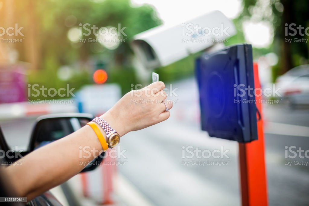 woman stop car and use key card to open the door for safety. driver...
