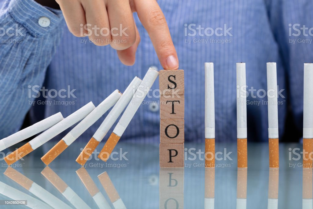 Woman Stopping Cigarette From Falling On Desk stock photo