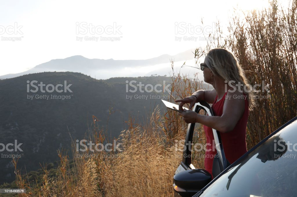 Woman stops car to look out at view while on her phone. She looks off...