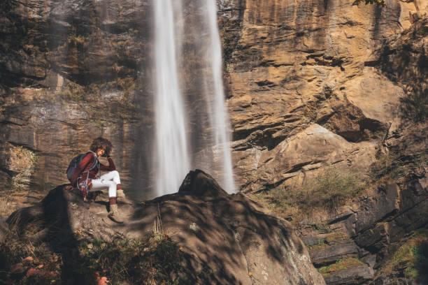 woman stops to view the waterfall up close stock photo