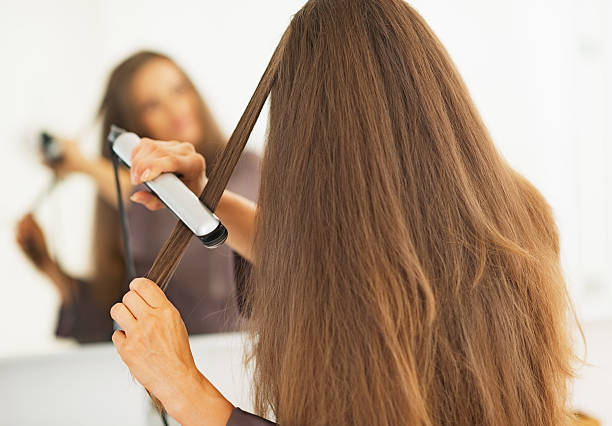 woman straightening hair with straightener . rear view stock photo