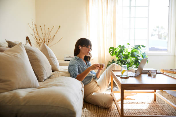 Woman streaming something on a laptop in her living room stock photo