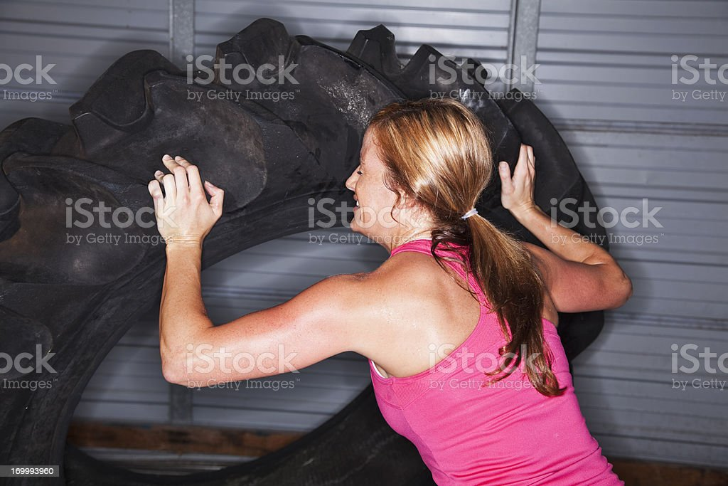 Woman strength training with tractor tire royalty-free stock photo